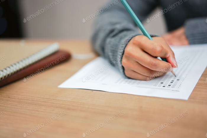 close up student woman hand using pencil for doing text exam after finish course online learning