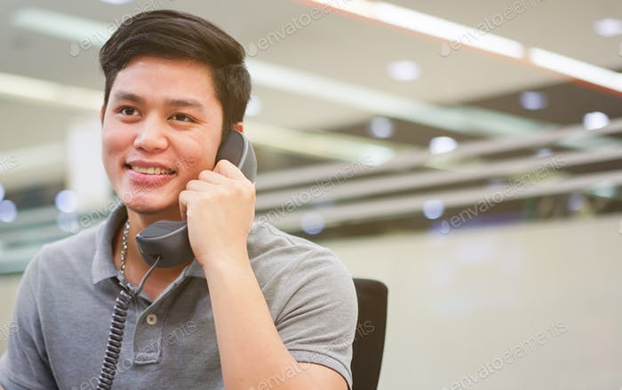 close up asian employee man holding handset telephone for call and talking at office concept