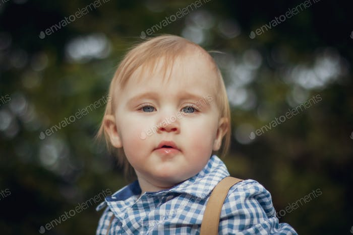 Toddler in a button up shirt with suspenders