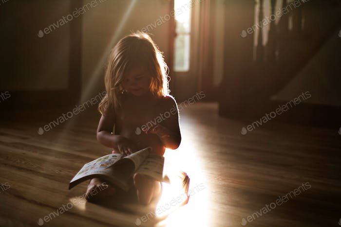Toddler reading book in a pocket of sunlight