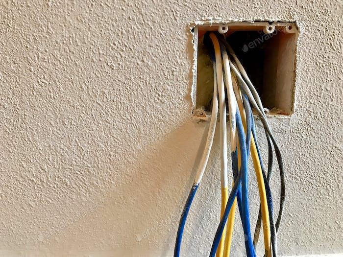 Elektrische Drähte hängen aus einer Wand, die repariert werden muss