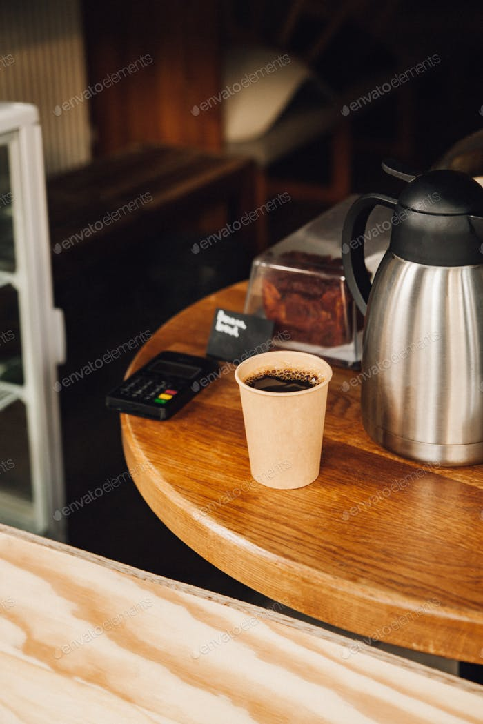 Take away coffee in an compostable to-go cup on the table