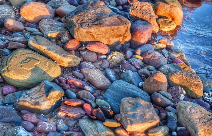 Colourful rocks on the shoreline in sunshine
