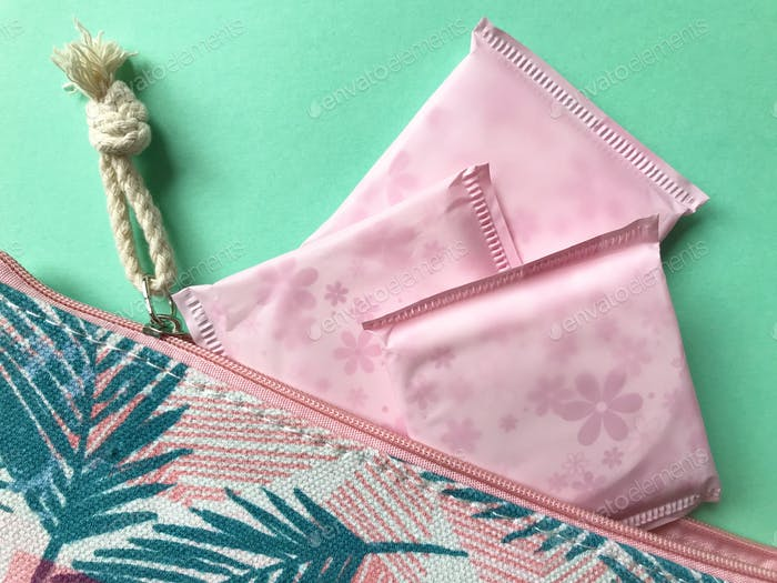 Women's Health : Menstruation. Sanitary pads and a make-up bag