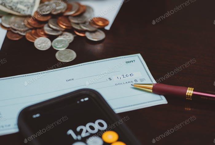 Completed check on a table with calculator on smartphone and coins on table