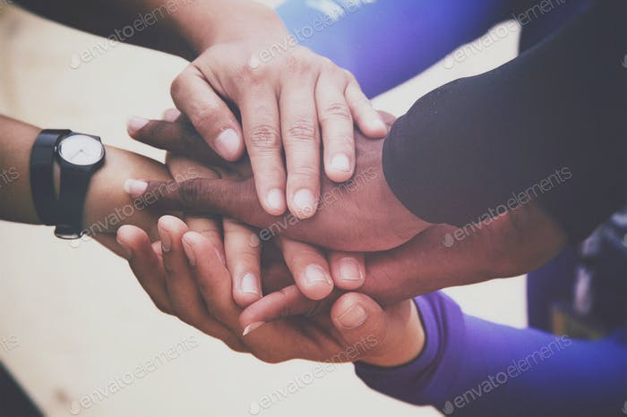 Diverse group of people holding hands in supportive gesture