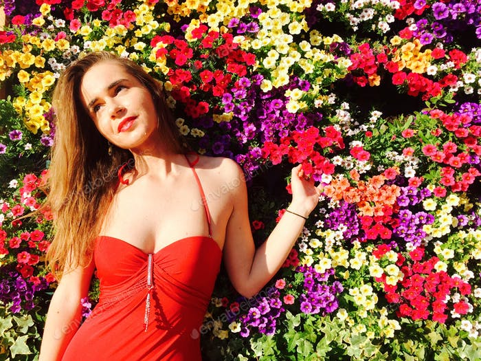 Woman in sexy red bathing suit standing against wall of multicoloured flowers