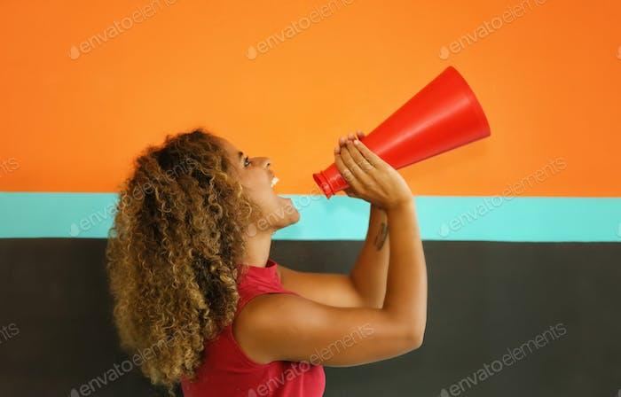 Mix race women shouting into megaphone