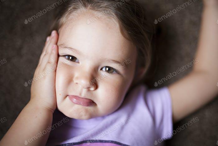 kleines Mädchen benimmt sich mit den Händen auf den Wangen.