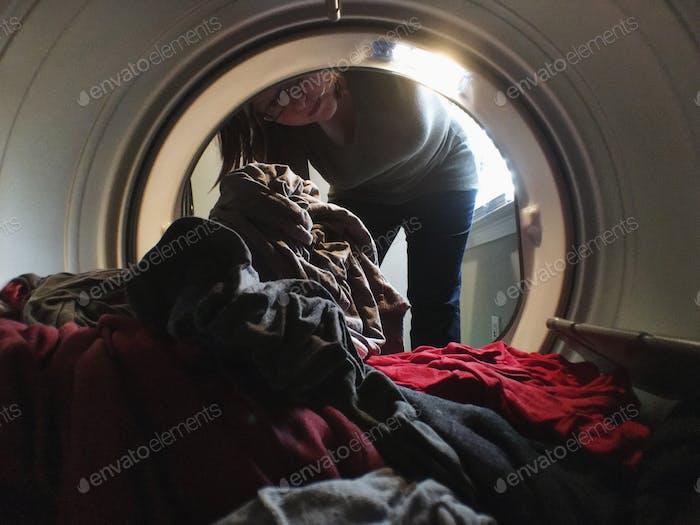 Mujer lavando ropa poniendo ropa en una secadora