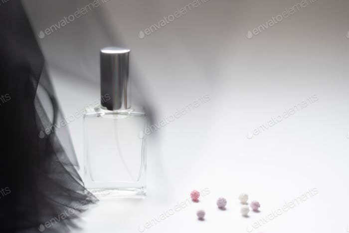Elegant perfume on a delicate black fabric. Summer style. Fashion accessories for girls.