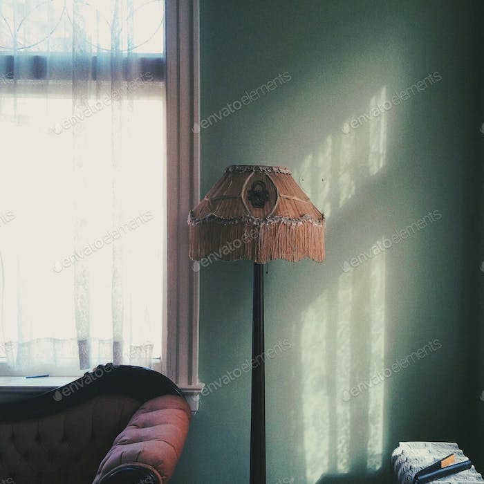 Light shines through a lace-curtained window, falling on an elegant lamp against a light green wall.
