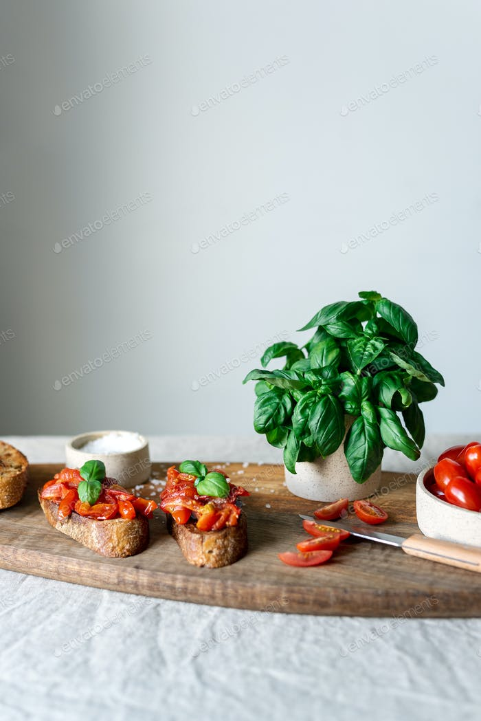 Classic bruschetta with tomatoes on a wooden cutting board.