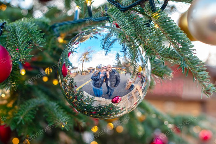 Couple making selfie in Christmas ball on Christmas traditional market