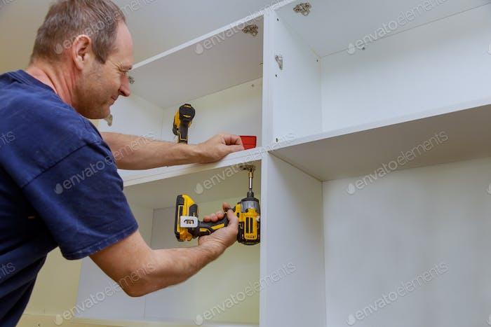 Carpenter installed a cabinet metal hinges for doors