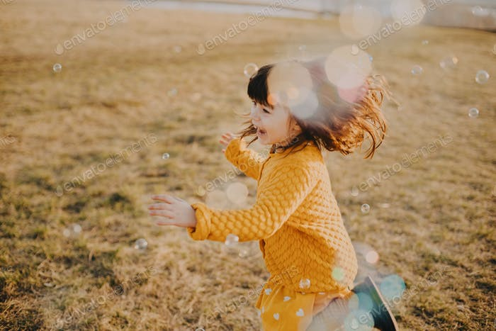 Little girl trying to catch bubbles on a field in sunny day