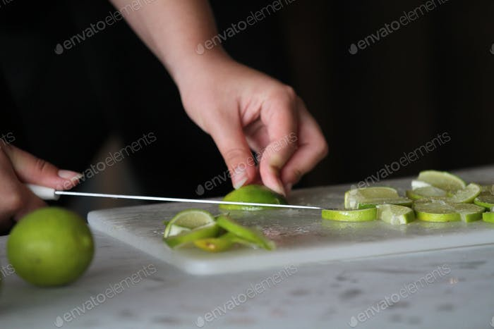 Fresh lime sliced up with knife, hands holding and knife slicing in action, kitchen work, bartender,