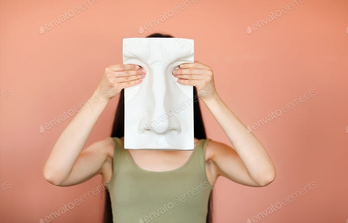 Unrecognizable female covering face with ceramic board in shape of human face while standing on pink