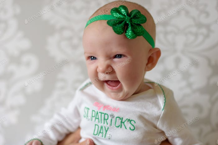 Closeup of happy baby girl wearing St. Patrick's Day outfit with shamrock headband