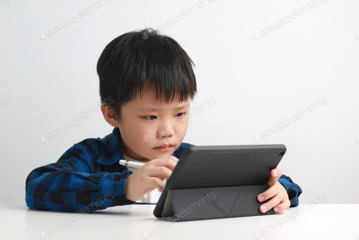 Young boy home schooling, using digital tablet
