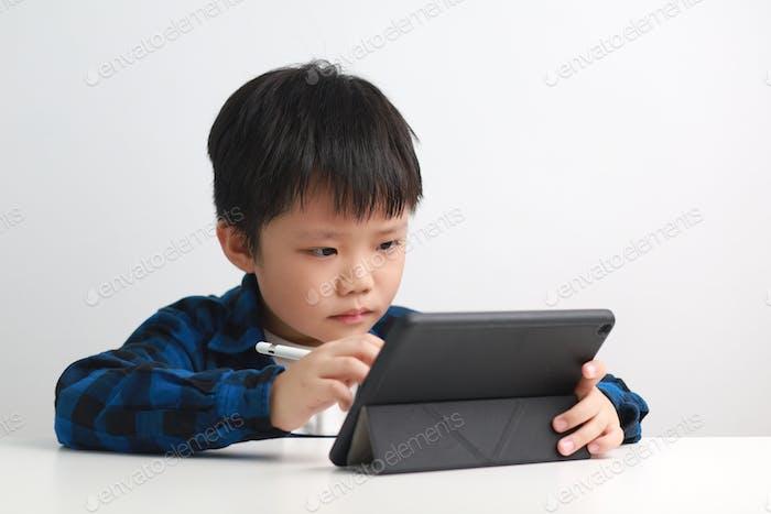 Junge zu Hause mit digitalem Tablet