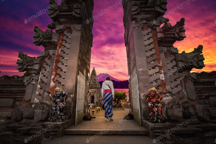 Backside of a young girl in front of a Bali temple with a beautiful purple sunset