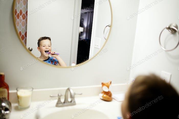 Junge Zähneputzen im Bad in einem runden Spiegel