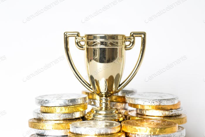 A gold trophy surrounded by prize-money for the winner of Victor of a competition