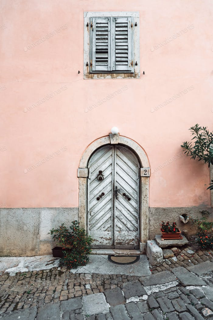 Rustic white door on pink house, old architecture, no people.