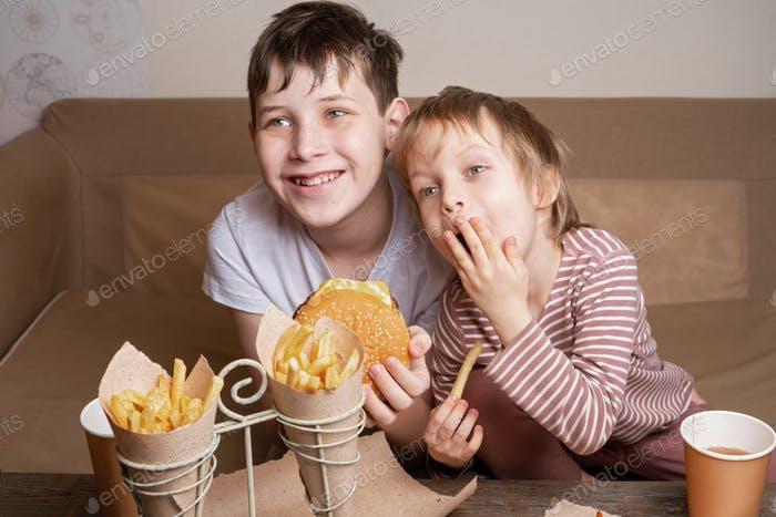 Two cute brothers eating junky food in front of TV. Family eating fast food and watching TV on sofa