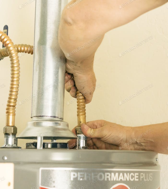 Adult male hands on water line going into a hot water heater