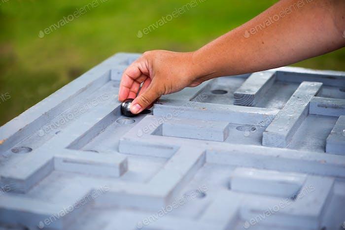 Nahaufnahme der glänzenden Metallkugel, die in einem Labyrinth Labyrinth navigieren