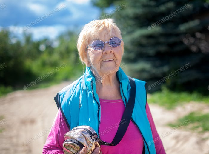 Fashionable and stylish great-grandmother 90 years old walking on a summer day.