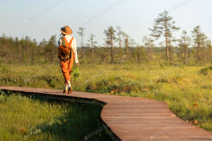 Woman naturalist exploring wildlife and ecotourism adventure walking on path through peat bog swamp