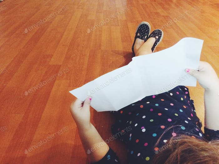 Little girl reading a paper