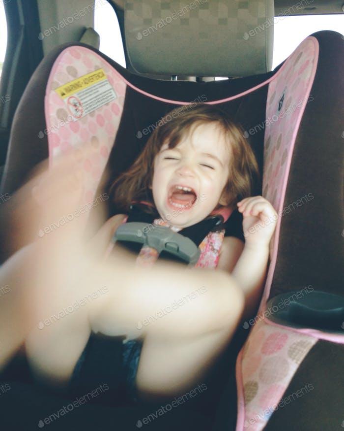 Niño niña en el asiento de coche, arrojando berrinche