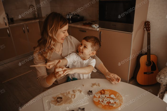 Beautiful mother bakes cookies with her son in the kitchen at the table