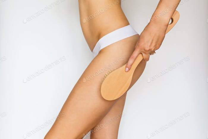 Woman making anti cellulite massage with natural dry brush on white background