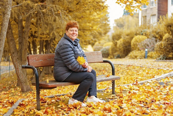 Adult senior beautiful 60 years old woman enjoying golden autumn sitting on wooden bench in the park