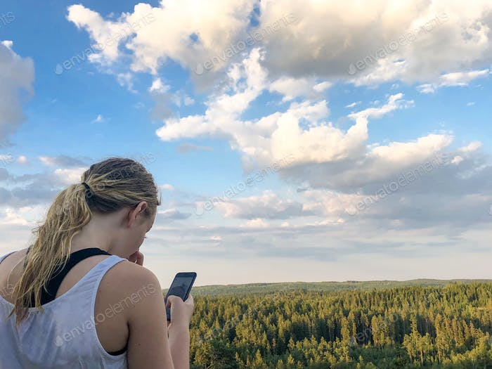 Girl using her phone to take photos over the views