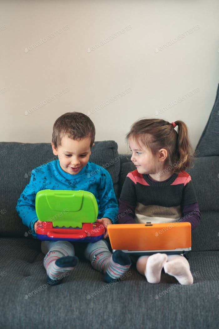 Two children playing with laptops learning basic digits, characters, sounds and images
