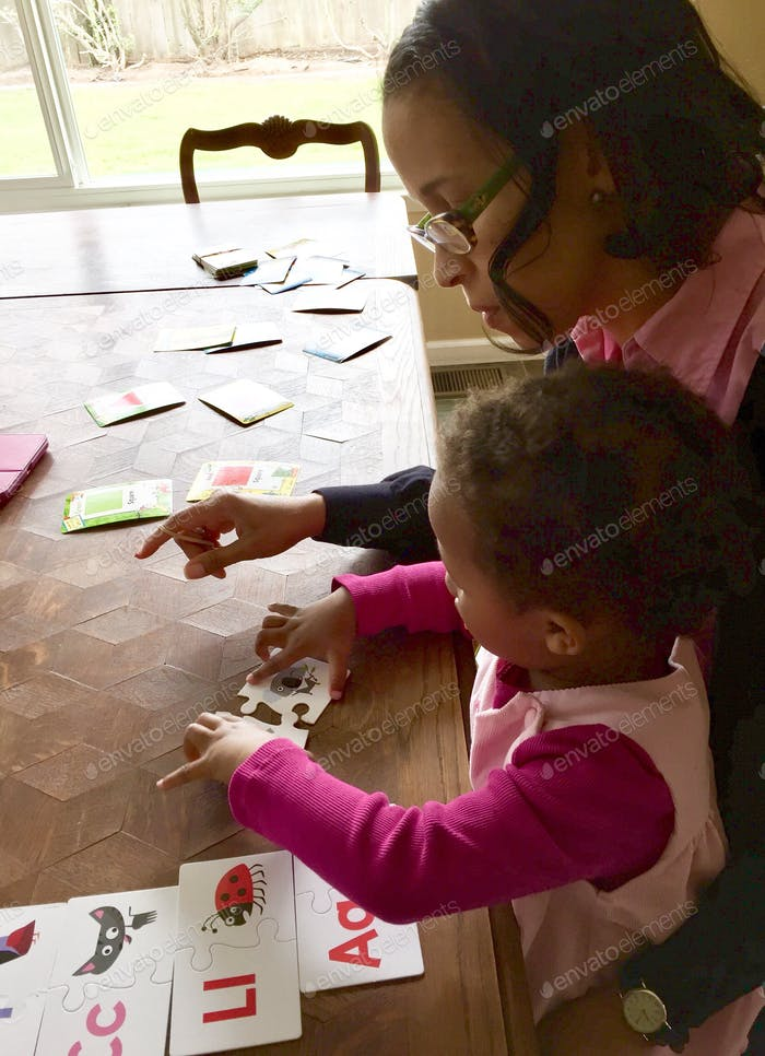 Mother teaching toddler girl at home