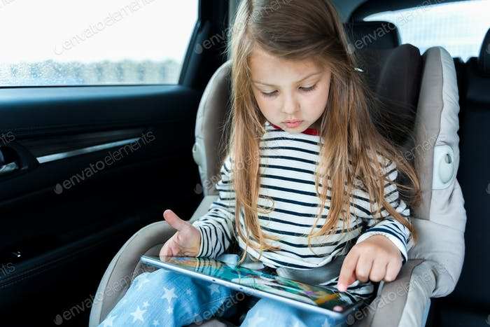 Little cute caucasian girl is driving in car. Online school learning,education.Playing video games i
