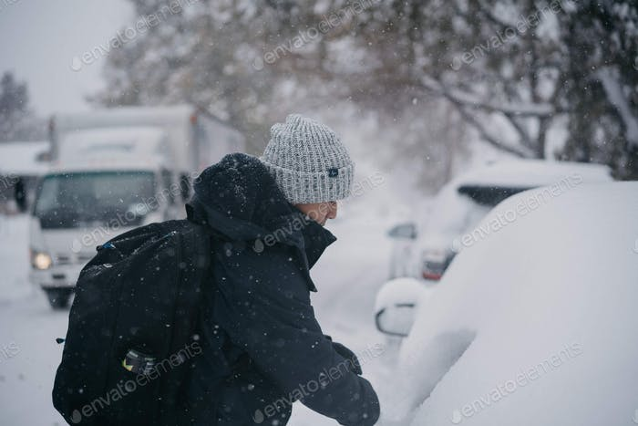 Dusting off snow on top of car storm in winter