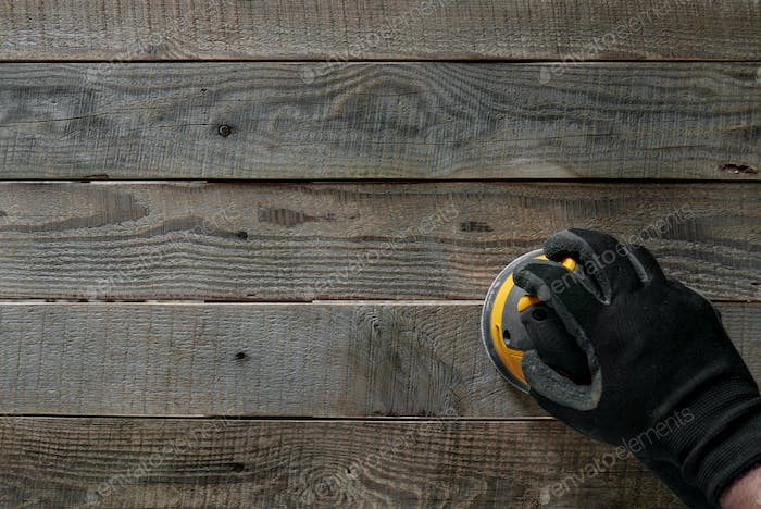 Hand in a glove holding a random orbital sander while sanding wooden boards.