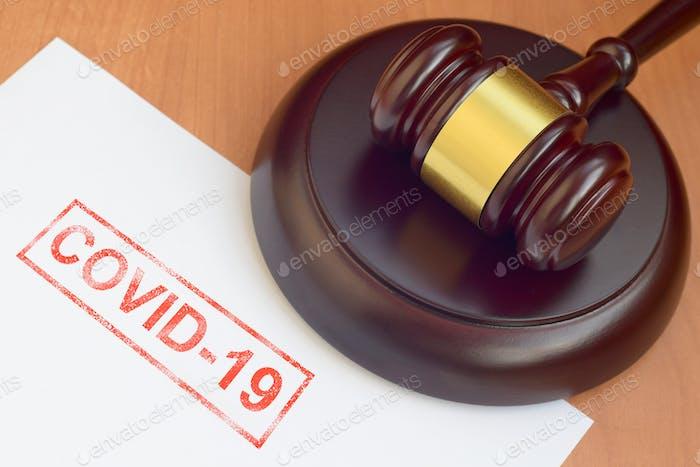 Mazo de justicia y documento en blanco con sello rojo Covid-19 de cerca