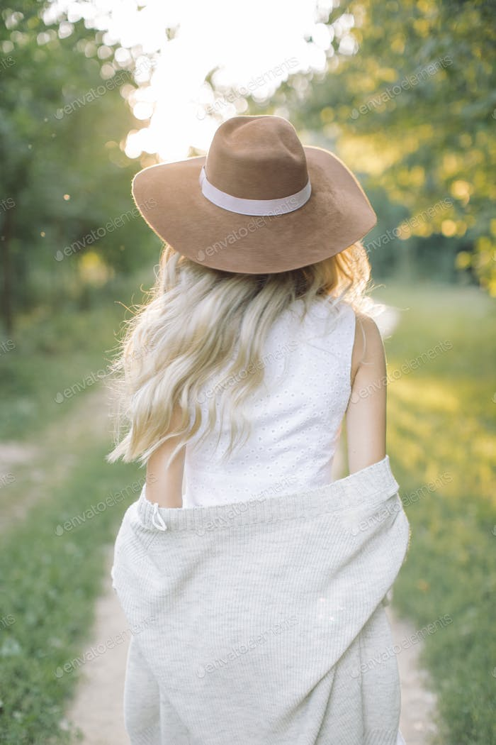 View from behind of young woman in hat walking in the park.