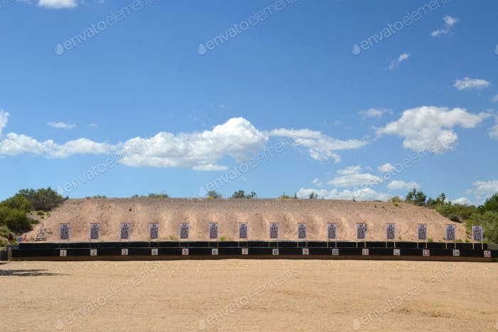 Paper targets at a gun range for target practice firearms training with a gravel berm behind it.