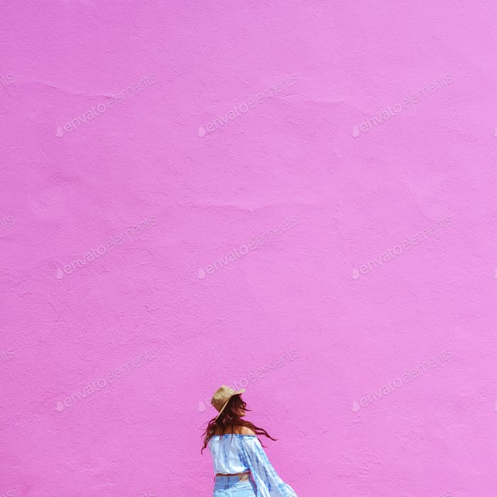 Pink wall in Los Angeles with Fashion Blogger dressed in latest summer trends.