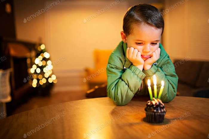 sad little boy crying over his birthday cake because no one came to his birthday party